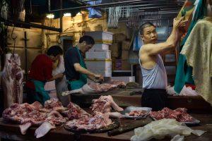 Butchers at work at pork butcher shop on Bowrington Road in Causeway Bay, Hong Kong