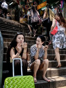 Two Chinese tourists taken time out on the Pottinger Street steps in Central, Hong Kong