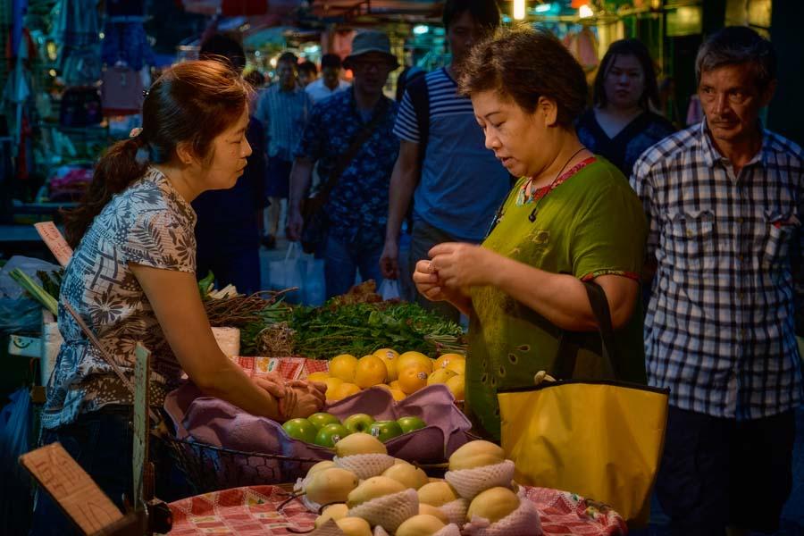 Two women sharing a moment on Reclamation Street in Yau Ma Tei, Hong Kong