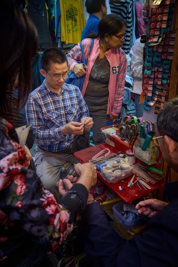 Watch repairman repairing watches in a stall off Wanchai Road in Wanchai, Hong Kong
