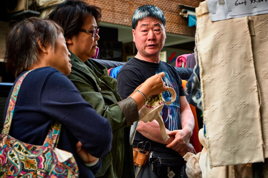 A haberdasher in conversation with customers in Sham Shui Po, Hong Kong